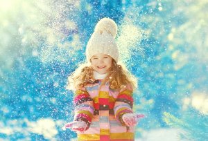 Happy child having fun playing with snow in winter day